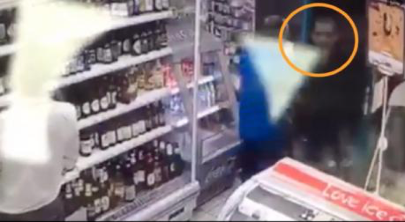 Young man is shown walking into a small convenience shop.