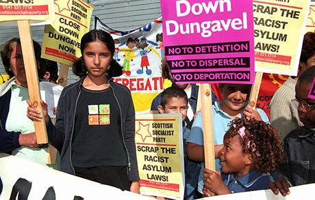 Children protest with signs and placards. Signs read No Detention, No Deportation