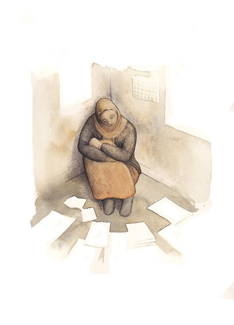 Woman sitting along in a corner. Surrounded by sheets of paper.