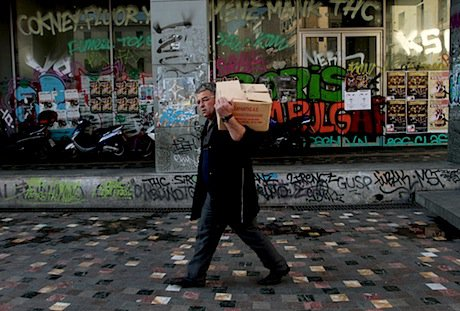 A worker outside a closed shop in Athens. Demotix/Panayiotis Tzamaros. All rights reserved.