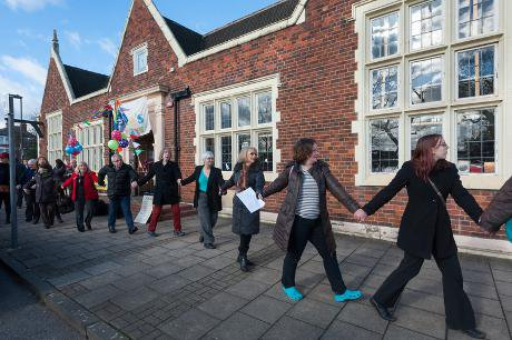 Library supporters link arms and walk past the frontage of the Friern Barnet Community Library