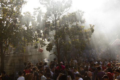Light rays shine through trees onto Gezi Park crowds with objects caught in mid air