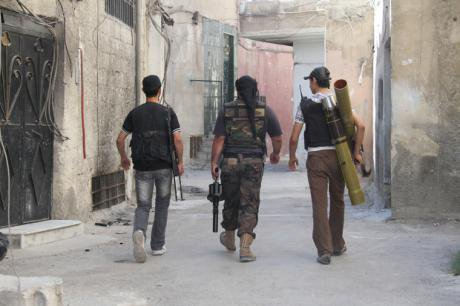 Free Syrian Army fighters carry their weapons to the frontline in Damascus