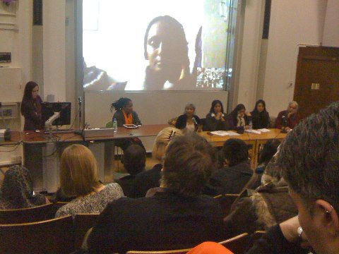 Panel of women with a projector screen behind them