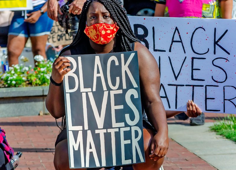 A woman holds a placard at a Black Lives Matter protest in Alabama, 2020.