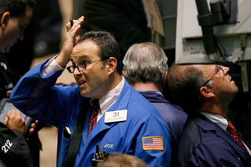 A trader on the New York Stock Exchange rubs his forehead and looks stressed