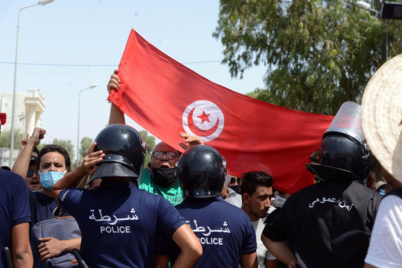 Police stand in front of clashes between citizens and members of the Ennahda Movement and the Al Karama Coalition.photo