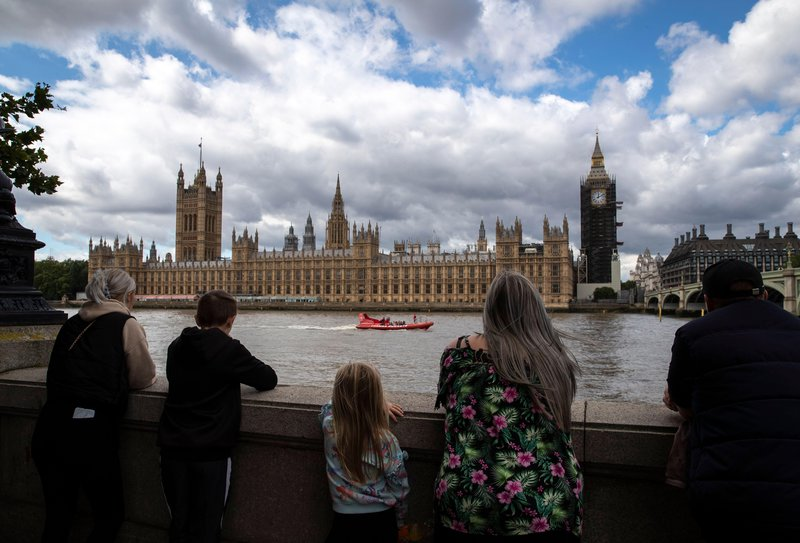 People stand in front of the Houses of Parliament in London