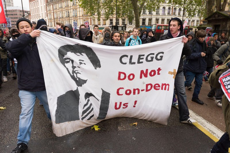 Protesters hold a banner reading 'Clegg: Do not Con-demn us'