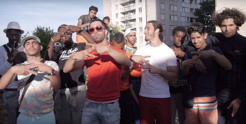 """Ademo (orange T-shirt) and N.O.S (white T-shirt) and their entourage forming with their hands a """"Z"""" signifying """"le zoo"""", to describe their hood, Les Tarterêts, in the 2015 debut single Le monde ou rien (The world or nothing) viewed over 100 million times"""