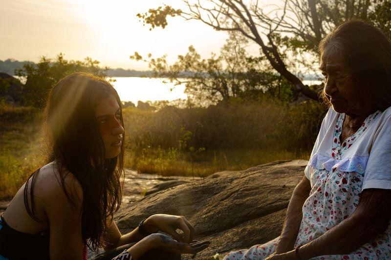 Lorena and Odete Kuruaya in nature with the sun setting in the background