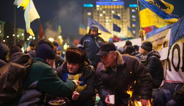 Protesters discuss current affairs near the fire at the Independence Square, Kiev.