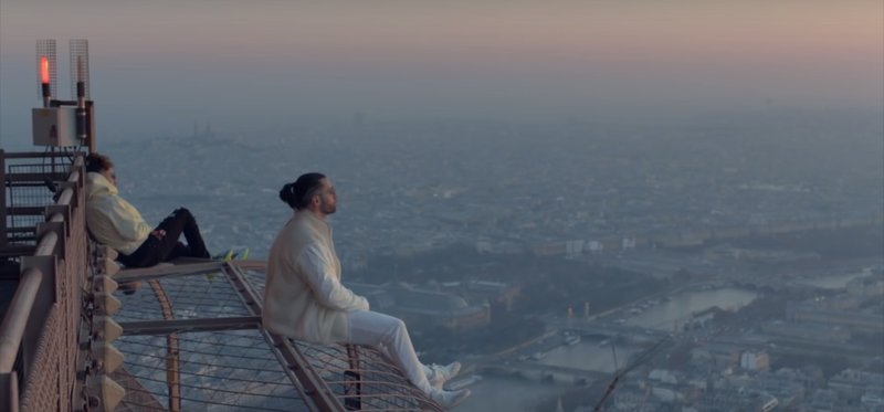 Ademo (white jeans) and N.O.S (black jeans) sitting on the top of the Eiffel Tower at dawn.