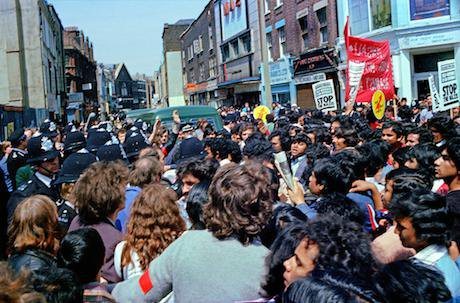 lead Crowd of young Bengali men fill East London street. Police officers in background.