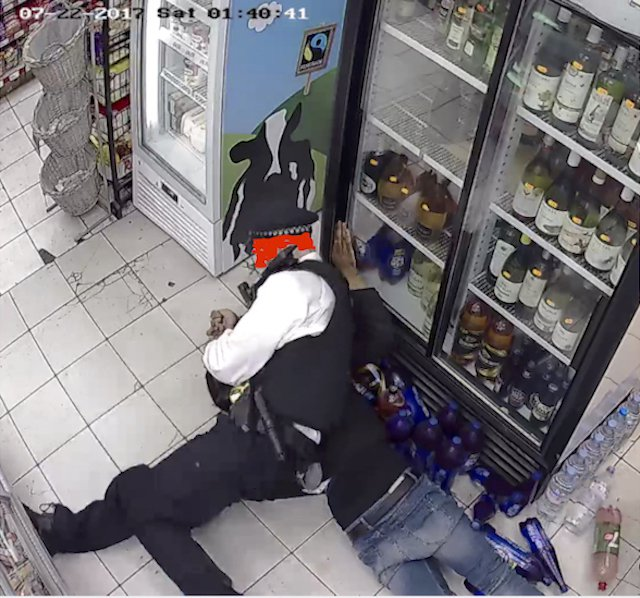 Police officer holding young man in headlock on the floor of a small shop.
