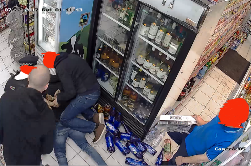 Two bystanders look on as two men restrain young man on shop floor.