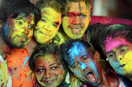 Some young people look cheerful after playing with powder dyes on the occasion of Holi festival at Dhakeshwari Temple in Dhaka