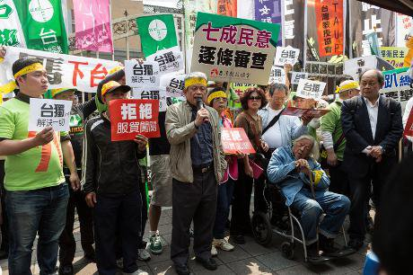 Political dissident Su Beng sits in a wheelchair listening to speeches at an anti-government protest