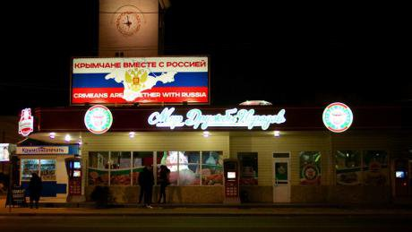 A sign above a restaurant reads in English and Russian 'Crimeans are together with Russia'