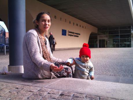 Roma woman and child beg in front of the European Commission building.