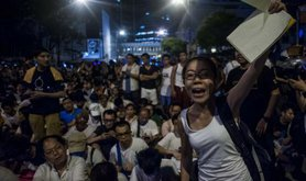 A demonstrator shouts as people sit in the streets during the rally for democracy.