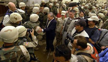 Secretary of Defense Donald H. Rumsfeld in 2004 poses for pictures with soldiers, marines and airman outside the Abu Ghraib Dete