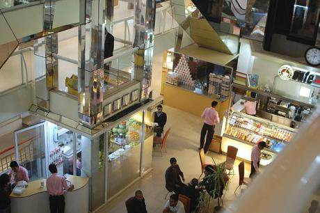 A shiny and modern coffee shop attended to by several employees in a large shopping centre.