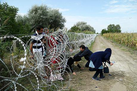 Syrian refugees cross into Hungary underneath the Hungary–Serbia border fence, 25 August 2015.
