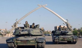 """US tanks pose in front of the """"Hands of Victory"""" monument, Baghdad, 2003. Wikimedia Commons/Public Domain."""