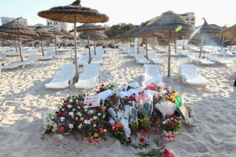 Tunisians lay flowes on the beach of the empty resort at Sousse.