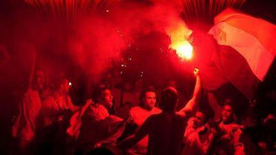 Black and red photo of men lit by a flare. Flag and flare held up.