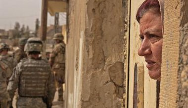 Woman stares into distance as - out of focus - soldiers retreat in background