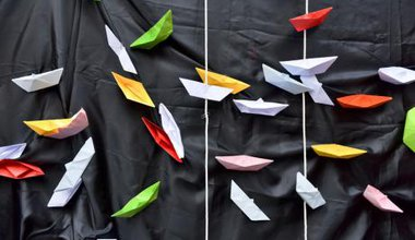 Protest at Palermo port, paper boats on black cloth representing the Mediterranean.