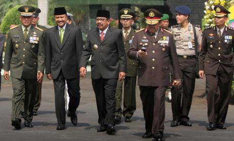 A group of civil, military, and police personnel are walking during an anniversary ceremony