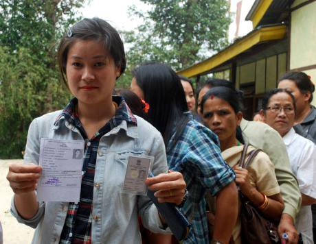 Young female voter showing her voter identity card in a queue in Sikkim, India