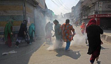 People in Kashmir, India, running through the streets in a cloud of tear gas