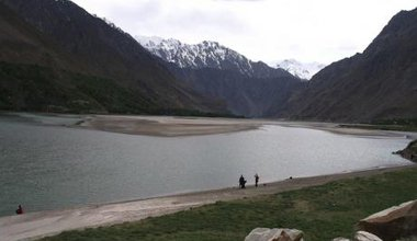 A narrow river runs through the picture, dividing the foreground and background. One side is Afghnistan, the other Tajikistan