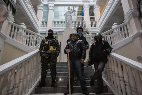 Three armed Maidan protesters stand on the steps of an occupied government building