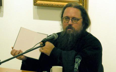 Andrei Kurayev at a talk. He is wearing black clothes, has an untamed beard and round glasses.