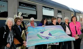 Women hold a WILPF banner in front of a train