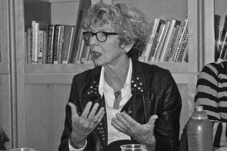 Photo of spectacled, curly-haired woman talking