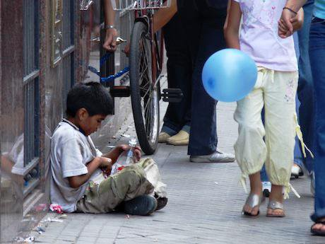Boy is ignored as he sits on the pavement in Rosario, Argentina. Pablo Flores/Flickr. Some rights reserved.