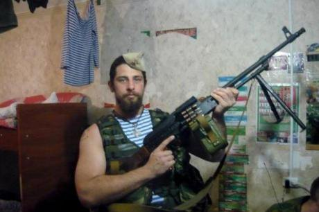 Rafael poses with a light machine gun in military fatigues.