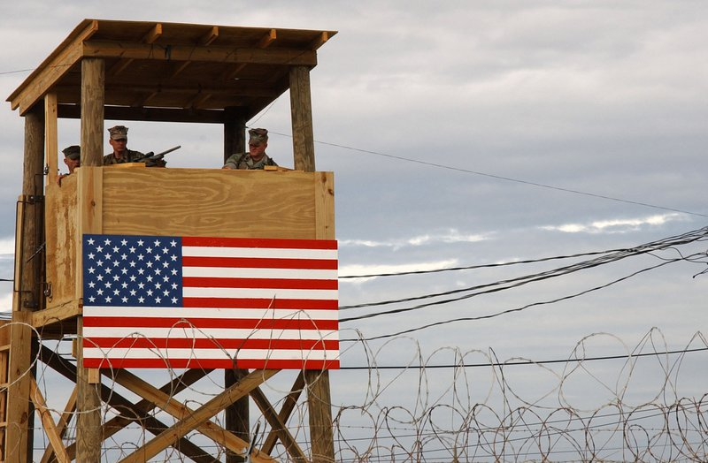 An American flag is draped over the side of a watchtower manned by armed guards
