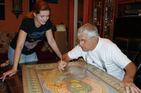 A an paints a religious icon as a young woman looks on admiringly.