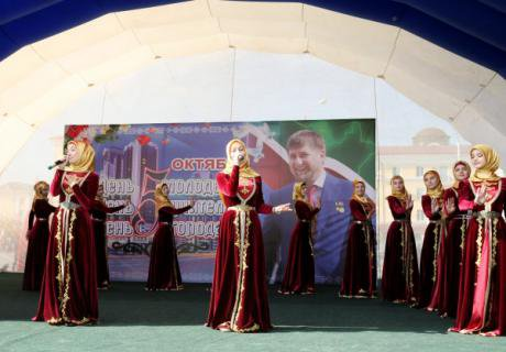 Women from Chechnya's ministry of culture displaying 'ideal' Chechen dress. Behind them is a picture of President Kadyrov.