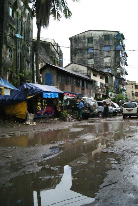 Muddy streets and worn infrastructure in Yangon. (Image by author)