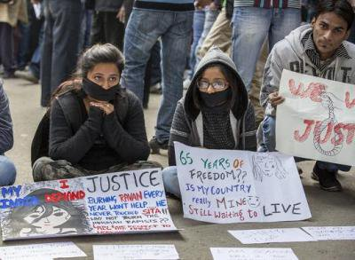 Two women sit with signs and symbolically gagged mouths alongside a crouching man with a sign.