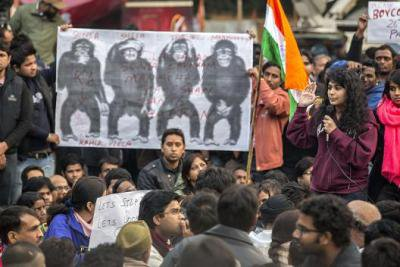 A young women speaks into a mic to a large crowd. Poster of the three wise monkeys behind, plus a 4th covering genitals.