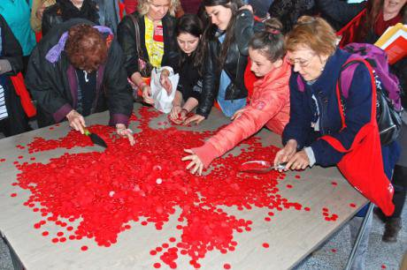 People working with piles of red coins